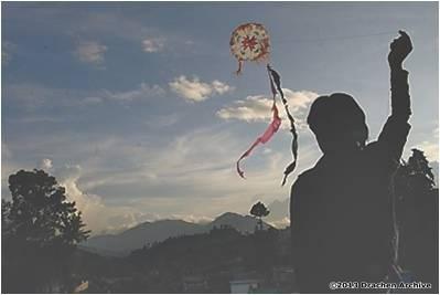 A child flies an octagonal kite in the Sumpango cemetery